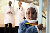 Young Kenyan boy looks closely at camera, two male medical workers in white coats stand in background