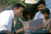 Outdoors, child seated at laptop is instructed by man in shirt and tie, man and child look on