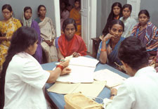 Two woman medical workers sit across table for two young Indian woman in saris, helping them fill out forms, many young women se
