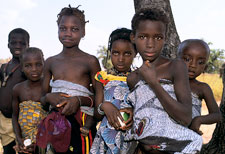Group of young African children gather to look at camera, some children carry younger children wrapped on their backs