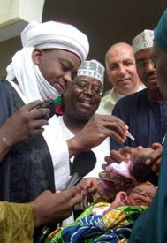 Group of men administer vaccine to infants