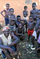 Group of young African children gather, ground littered with husks, one man seated on ground in front of boys