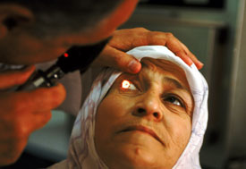 Older woman looks up, medical worker holds up her eyelid and uses instrument to shine light in her eye