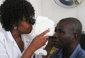 Woman medical worker uses large handheld tool to examine one eye of a male patient