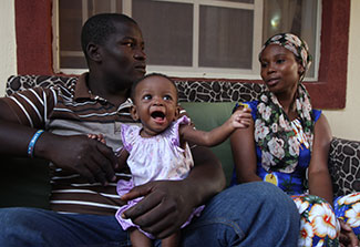 In Nigeria a father holds a happy young baby, seated next to mother