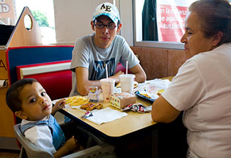 An older woman, teenage boy and young child in high chair eat a meal at a fast food restaurat