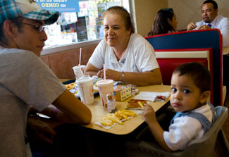 Woman, man and young child seated at booth in fast food restaurant with drinks and fries on table
