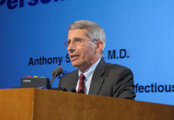 Dr. Anthony S. Fauci speaks into microphone at a podium, slide projected in background