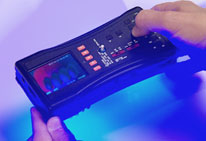 Close up of hands holding FDA Counterfeit Detection Device-3 CD-3, black electronic box with many buttons emits glow on bottom