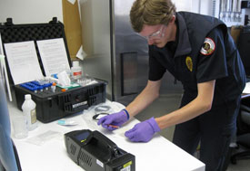Man leans over table, wears purple disposable gloves and protective glasses, performing test, large case with many bottles