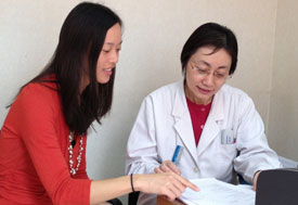 Dr Evelyn Hseih, pointing at paper, confers with Dr Zhang Pin