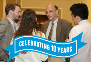 Fogarty Director Roger Glass speaks with Fogarty fellow and scholars, ribbon reads celebrating 10 years