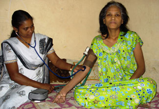 Older woman seated cross-legged on bed, looks at camera while medical worker takes her blood pressure
