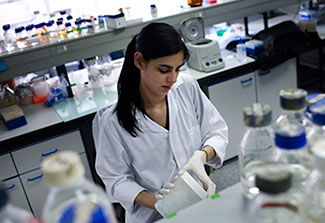 female researcher works in lab wearing white lab coat