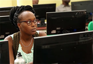 Female student working at a computer in a classroom.