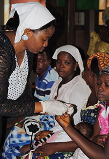 In Nigeria, woman tests an expectant mother for HIV, other expectant mothers in background