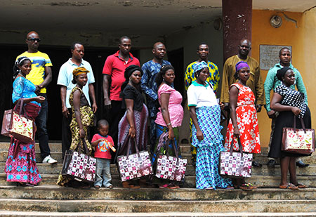 7 pregnant women line up on stairs holding shopping bags, men line up behind each of them