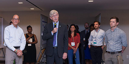 Dr Francis Collins holding microphone speaks to crowd of Fellows and Scholars during orientation, stands next to Dr Roger Glass