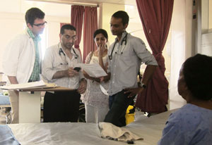 Man holds medical chart, three people look on, two wear stethoscopes, patient sits in foreground next to empty hospital bed