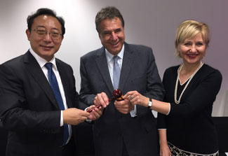 Dr. Xuetao Cao hands a gavel to Dr. Alain Beaudet, Dr. Glenda Gray looks on