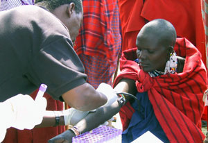 African woman extends arm to have blood drawn by a male medical worker at outdoor clinic