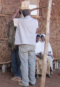 Man measures the height of another man, standing, women seated in background, outdoors next to a rough hut