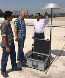 Three men stand next to equipment crate and tall silver metal tool measuring air quality