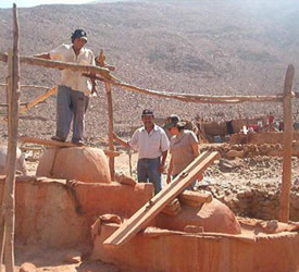 Three miners stand next to rough wooden supports and ramp, and dried red clay in front of dry, hazy hill