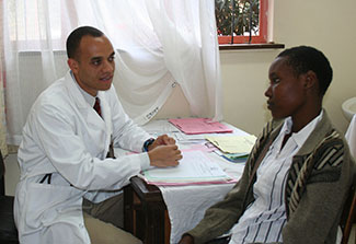 Researcher in clinic seated at a desk meets with young adult patient