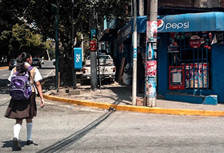 In Guatemala, a girl wearing backpack and school uniform crosses street toward market covered in ads for Pepsi and other product
