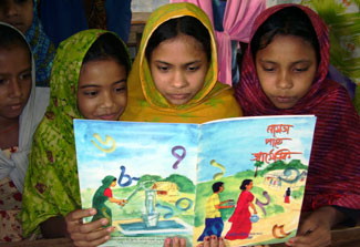 A group of young girls in Bangladesh reads a book together, illustrated book cover shows people pumping and carrying water