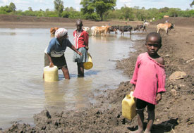 young girl in foreground carries plastic jug of water from muddy water source, woman and older girl in background fill jugs