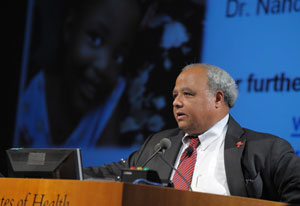 Ambassador Eric Goosby speaks at a podium at NIH, slide projected in background, picturing a young child