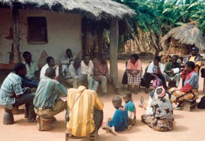 Large group of adults and children, seated on stools and dry dusty ground in circle, huts in background