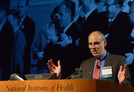 NICHD Director Dr. Alan E. Guttmacher speaking at a podium, slide projected in background