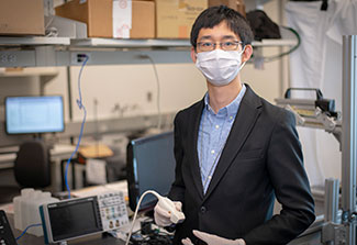 Dr. Haichong Zhang works with computer equipment in a lab wearing a mask.