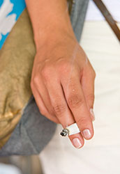 Close-up of hand holding a smoking cigarette
