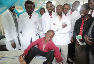 Smiling, health-looking young African boy in hospital bed surrounded by many healthcare workers