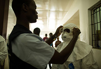 Healthcare workers put on personal protective equipment in Liberia