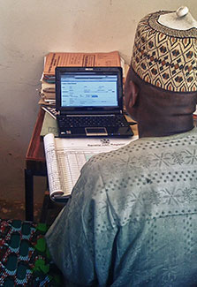 View over shoulder of man entering health data on a laptop
