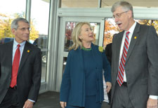 Dr Anthony Fauci walks next to Secretary Hillary Clinton, who speaks with Dr. Francis Collins while exiting a building.