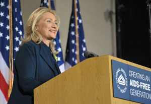 Secretary of State Hillary Clinton smiles from a podium with NIH logo, American flags in background