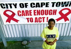 Woman wearing tshirt reading HIV positive stands in front of large sign reading city of cape town, care enough to act