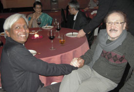 Dr. K. VijayRaghavan and Dr. Maharaj K. Bhan seated at a banquet table shaking hands