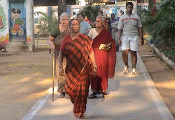 Indian people of a variety of ages walk on concrete path through outdoor park