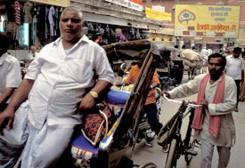 Indian men in busy street, one walks with bicycle