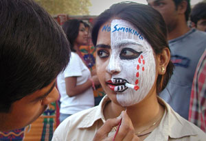 Young Indian woman receives face painting from may, half of face covered with white makeup, fake cigarette, reads no smoking