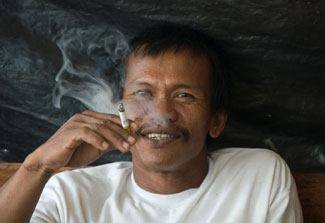 Indonesian man holding smoking cigarette smiles at the camera, puffs of smoke visible