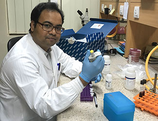 Dr. Mohammad Aminul Islam works with samples in a lab