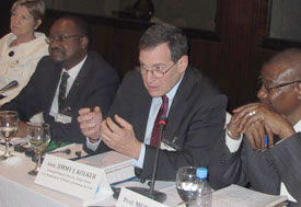 U.S. Ambassador to Mali Jimmy Kolker speaks, seated at conference table, people seated on both sides